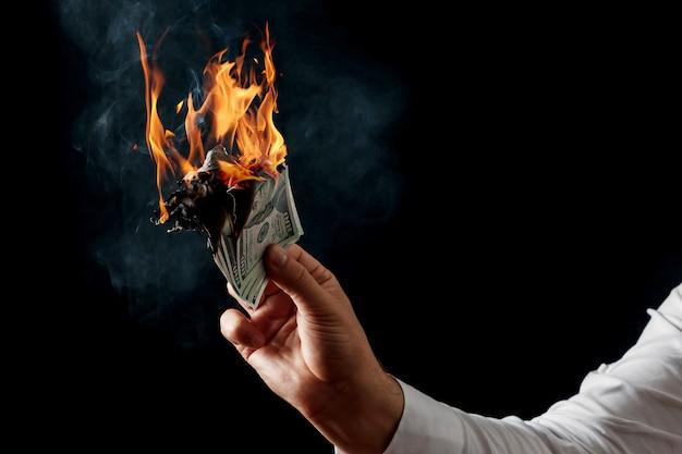 Ein mann hält brennendes geld in der hand