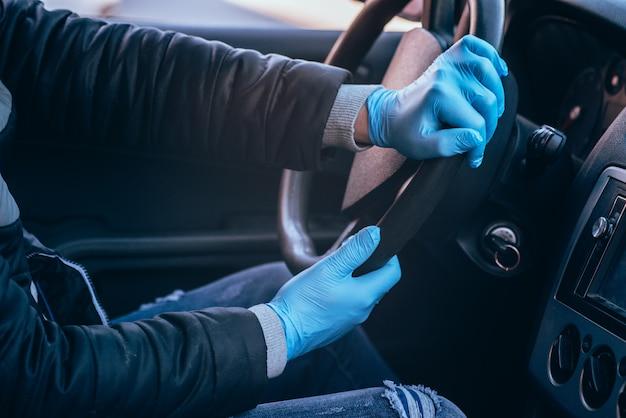 Ein mann hält das lenkrad eines autos in medizinischen schutzhandschuhen. hände nahaufnahme. sicheres fahren in einem taxi während der pandemie des coronavirus.