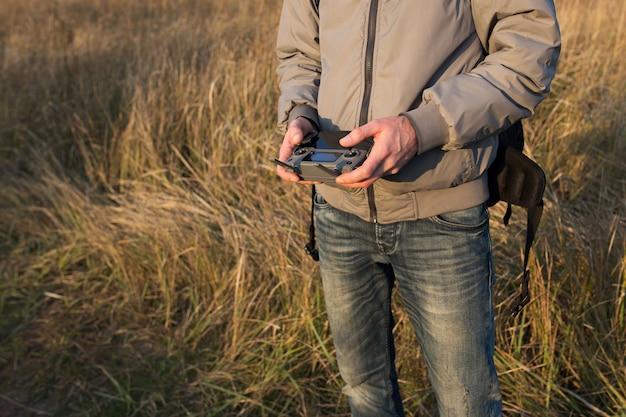 Ein mann hält ein drohnen-bedienfeld in der nähe.