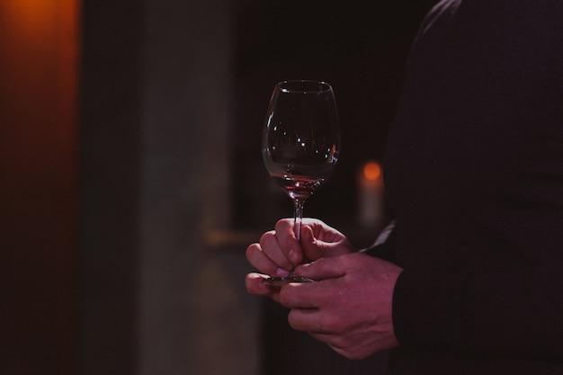 Ein mann hält ein glas rotwein