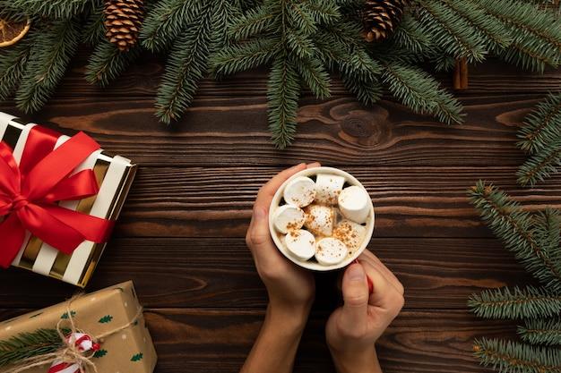 Ein mann hält ein heißes weihnachtsgetränk mit marshmallows und zimt in den händen