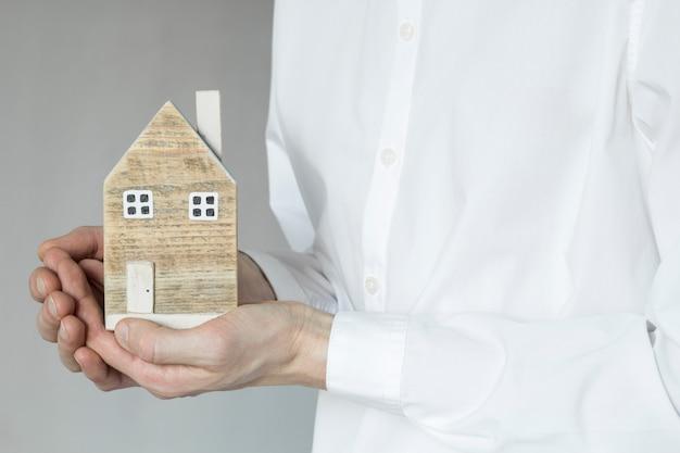 Ein mann hält ein musterhaus in seinen händen. kauf von immobilien, hypotheken. versicherungsvertreter
