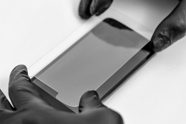 Ein mann hält ein schutzglas für ein smartphone.