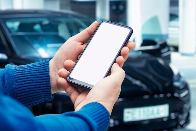Ein mann hält ein smartphone mit einem weißen bildschirm