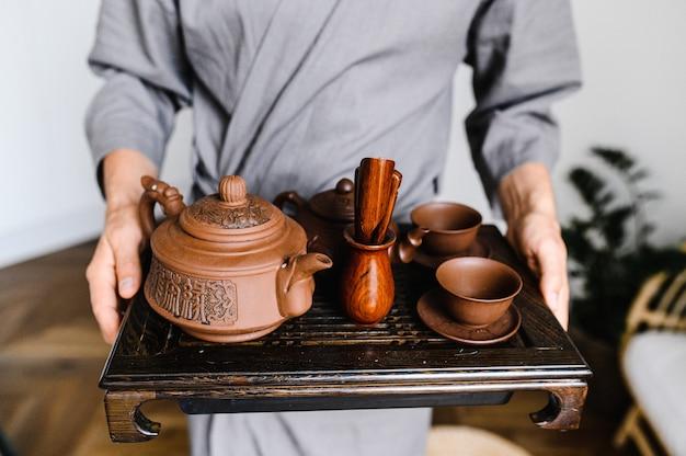 Ein mann hält ein tablett mit einem set für eine chinesische teezeremonie.