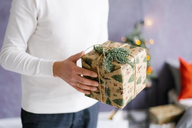Ein mann hält ein weihnachts- oder neujahrsgeschenk in den händen.