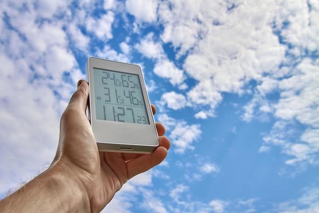 Ein mann hält ein wetterstationsgerät auf einem hintergrund von himmel und wolken