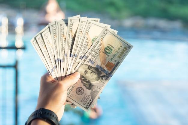 Ein mann hält eine dollarbanknote für einen geschäftsaustausch in der hand.