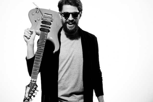 Ein mann hält eine gitarre in seinen händen schwarze lederjacke dunkle brille musikleistung hellen hintergrund. hochwertiges foto