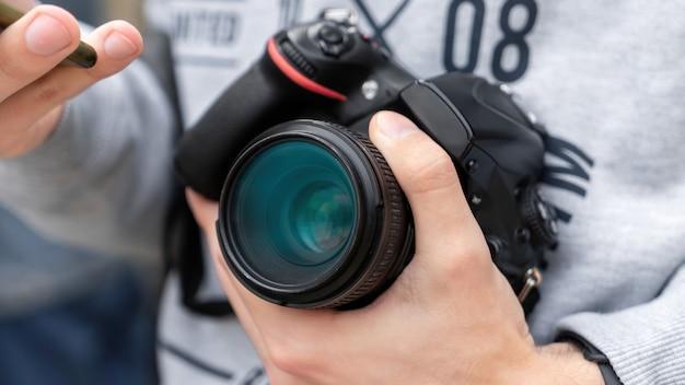 Ein mann hält eine kamera in der nähe der brust