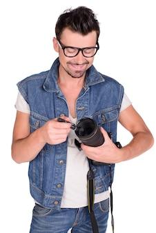 Ein mann hält eine kamera in seinen händen und lächelt.