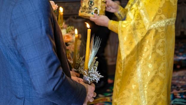 Ein mann hält eine kerze, orthodoxer priester, der in einer kirche dient. hochzeitszeremonie