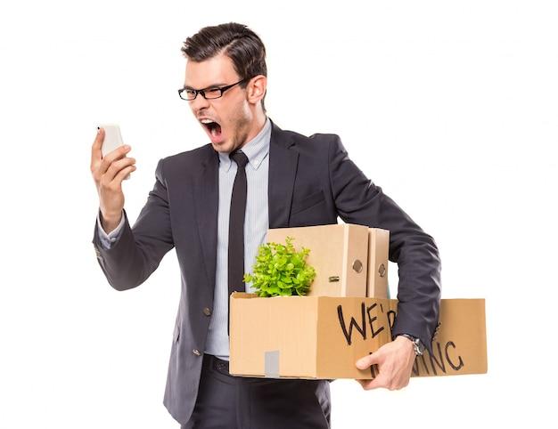 Ein mann hält eine kiste mit sachen wegen entlassung.