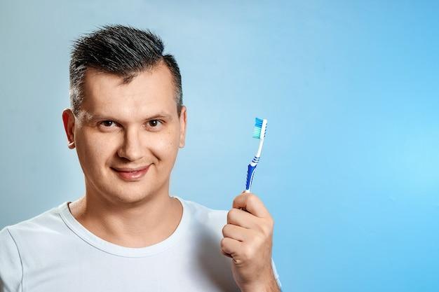 Ein mann hält eine zahnbürste und putzt sich die zähne.