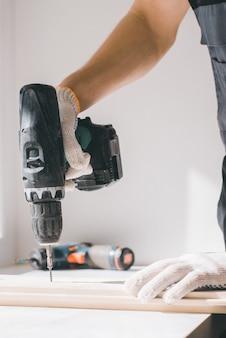 Ein mann hält einen akkuschrauber in der hand und wickelt die schraube in ein brett.