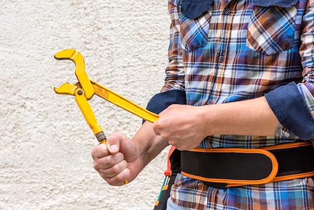Ein mann hält einen gasschlüssel in den händen.