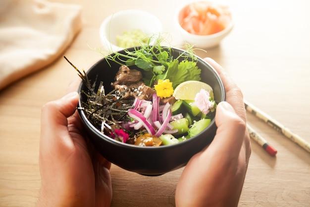 Ein mann hält einen poke-salat mit rindfleisch in einer schüssel in den händen. zutaten rindfleisch, nameko-pilze, kirschtomaten, reis, gurke, rote zwiebel, sesam, koriander, limette. asiatisches salatkonzept.