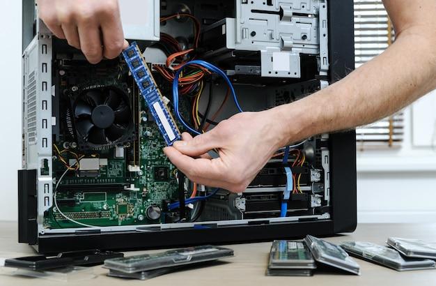 Ein mann hält einen ram-steckplatz in der hand, um den computer zu aktualisieren.
