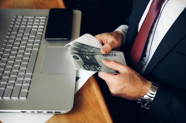 Ein mann hält einen stapel bargeld und zählt ihn in nahaufnahme. seitenansicht
