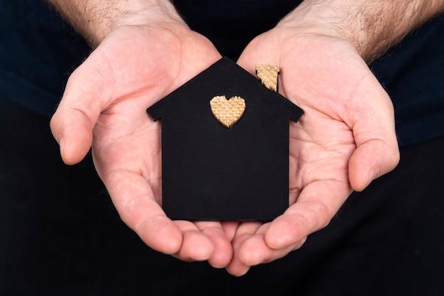 Ein mann hält in seinen händen ein flaches modell eines hauses an einer dunklen wand. familienkreditkonzept