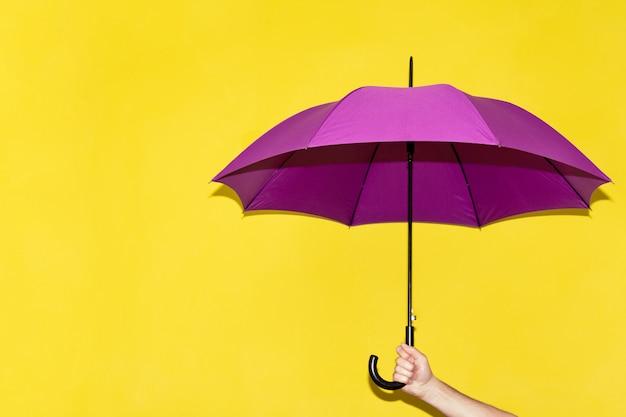 Ein mann hält in seiner hand einen purpurroten regenschirm