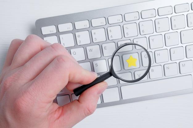 Ein mann hält mit seiner hand eine glaslupe über einem abstrakten stern auf einer tastatur. assessment-analyse. flach liegen.