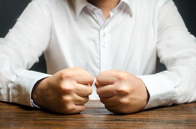 Ein mann hält seine geschlossenen fäuste auf dem tisch. das ende der geduld. es ist unmöglich, es zu ertragen