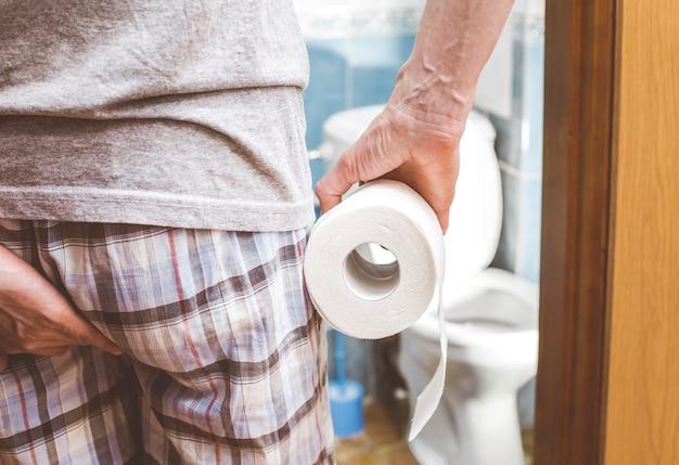 Ein mann hält toilettenpapier. durchfall. verstopfung konzept.