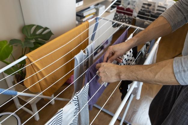 Ein mann hängt die gewaschene wäsche am trockner auf, der sich in einem raum der wohnung befindet. hygienekonzept, hilfe für männer zu frauen rund ums haus, rollenwechsel, tägliche reinigung. horizontal.