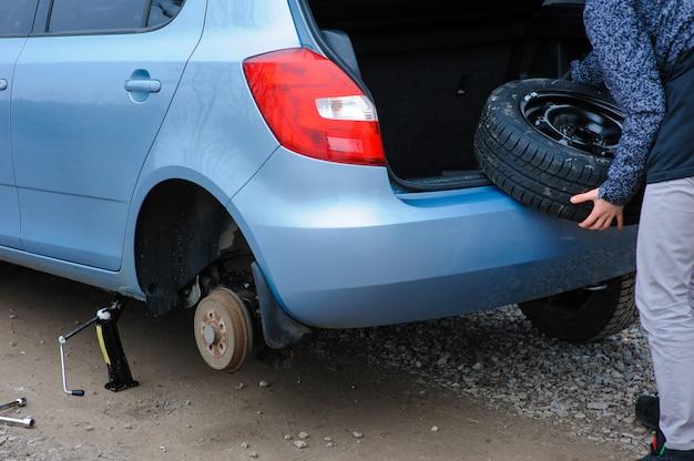 Ein mann hat ein rad an einem auto gebrochen und es auf der straße selbst gewechselt.