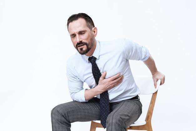 Ein mann hat ein schlechtes herz. er hält seine hände an seine brust.