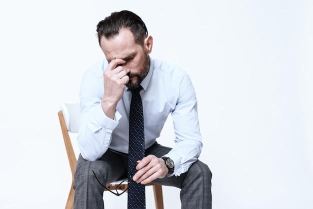 Ein mann hat kopfschmerzen. er hält seine hände auf seinem kopf.