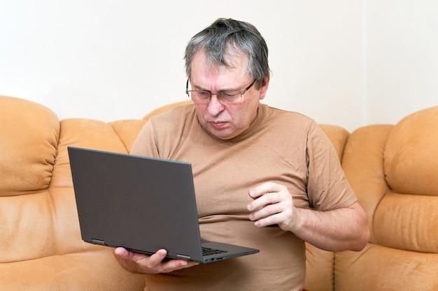 Ein mann im alter, der auf devani sitzt, schaut sich die nachrichten auf einem laptop an