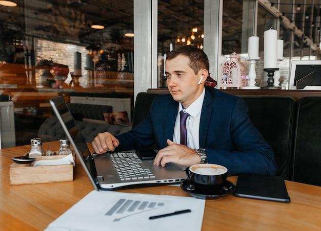 Ein mann im anzug arbeitet in einem café an einem laptop. geschäftsmann mit laptop.