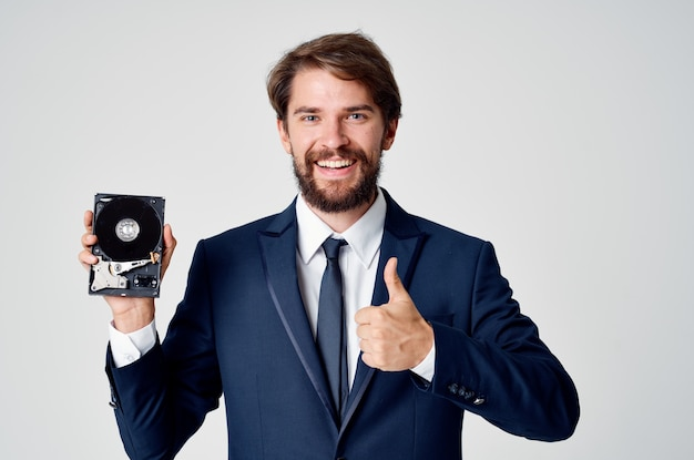 Ein mann im anzug hält eine nicht zusammengebaute festplatte in der hand und einen grauen hintergrund