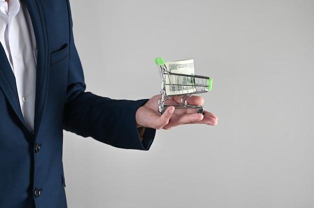 Ein mann im anzug hält einen einkaufswagen mit dollars in den händen
