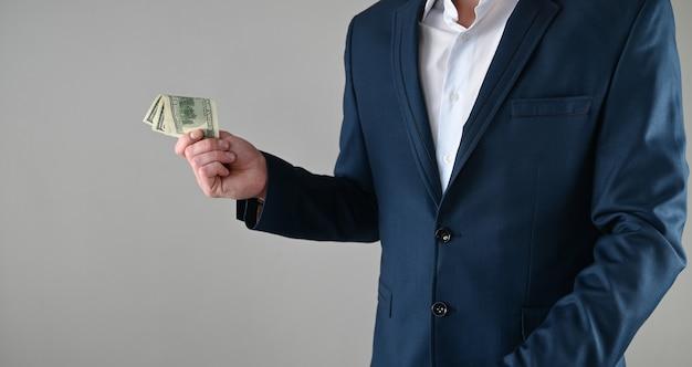 Ein mann im anzug hält geld in den händen
