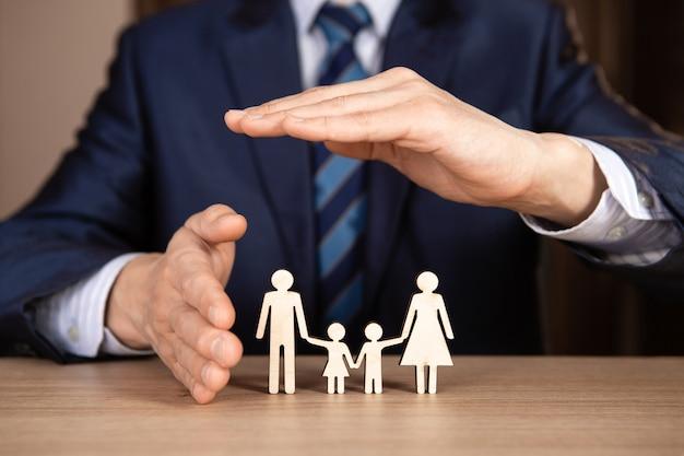 Ein mann im anzug hält hände in form eines hauses über der familie. versicherungskonzept.