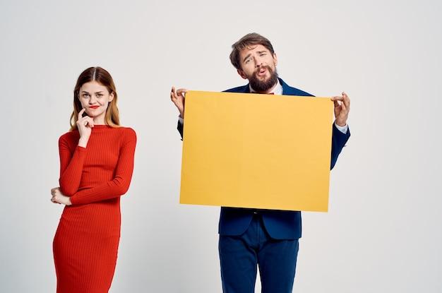 Ein mann im anzug neben einer frau in einem roten kleid gelbe mockup-plakatwerbung