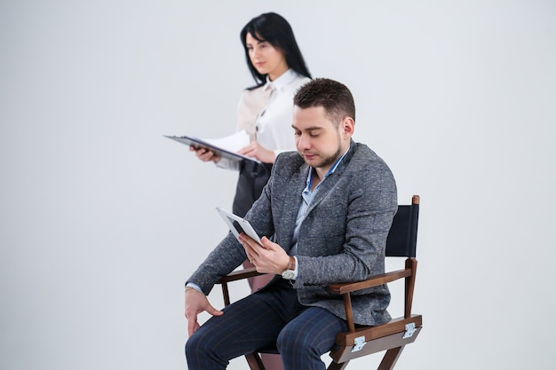 Ein mann im anzug sitzt mit einem tablet auf einem schwarzen stuhl und eine frau wirft dokumente. zukünftige geschäftsleute sind nervös und sprechen über ein neues projekt. geschäftspartner auf weißem hintergrund.