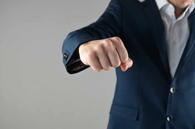Ein mann im anzug zeigt seine faust