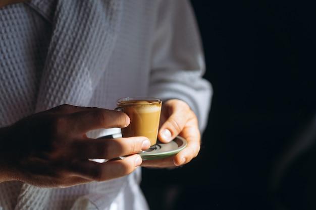 Ein mann im bademantel hält eine kleine tasse kaffee in der hand