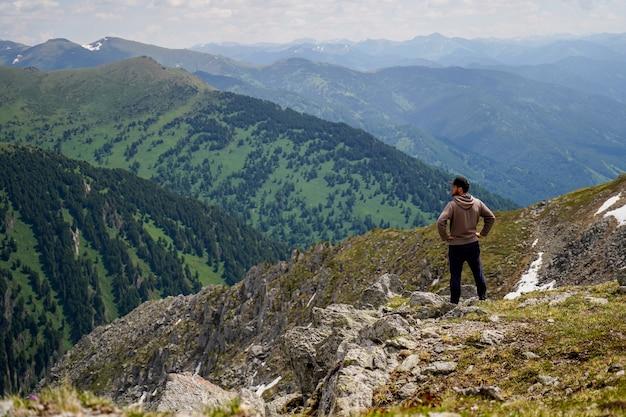 Ein mann im braunen kapuzenpulli, der an im berghang vor bergen steht