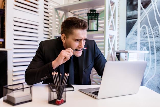 Ein mann im büro beißt einen bleistift