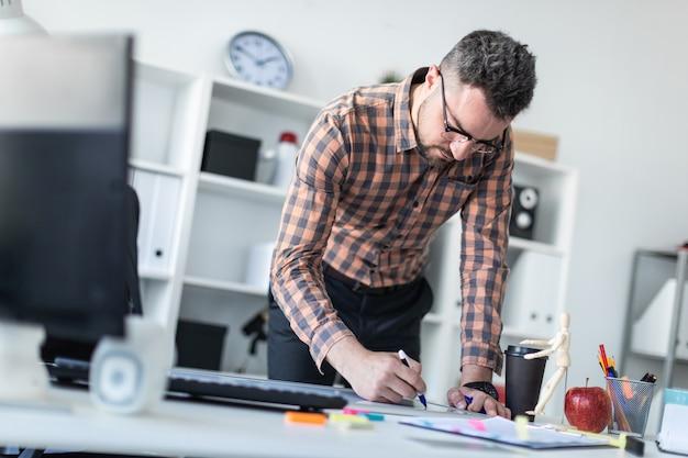 Ein mann im büro steht neben dem tisch und zeichnet einen marker auf die magnettafel.