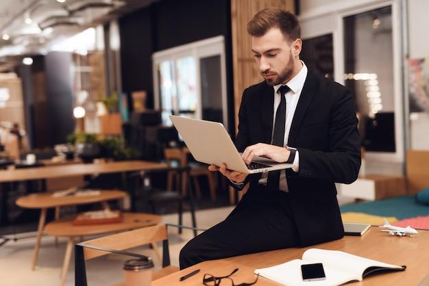 Ein mann im business-anzug sitzt mit einem laptop auf dem tisch.