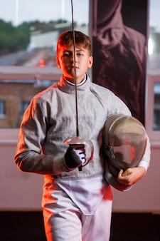 Ein mann im fechtanzug mit einem schwert in der hand, neonlicht. ein junges modell trainiert und trainiert in bewegung, aktion. sport, jugend, gesunder lebensstil.