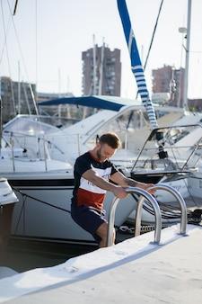 Ein mann im hafen, der die yacht für die reise vorbereitet