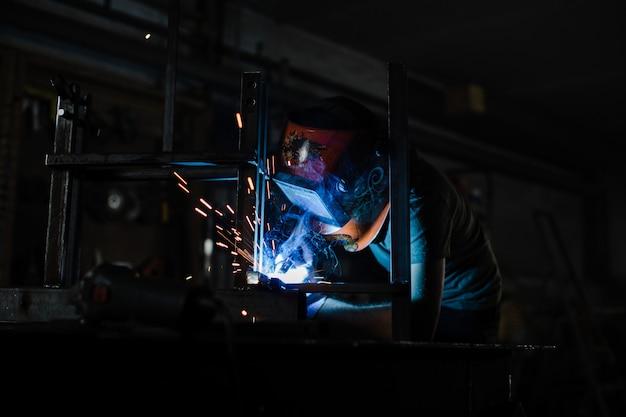 Ein mann im helm arbeitet mit einem schweißgerät