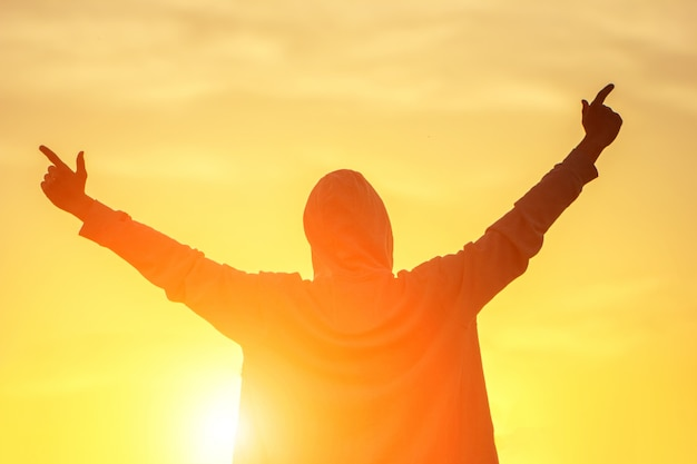 Ein mann im licht des sonnenuntergangs mit seinen händen